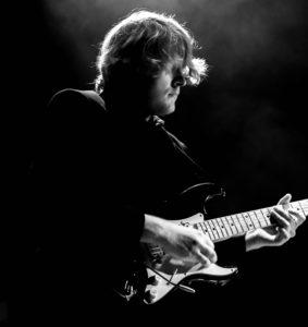 et sort hvit bilde av Håvard som spiller gitar