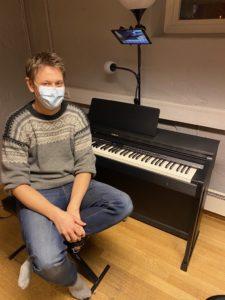 et bilde av en pianolærer som underviser på nett, med et kamera på stativ over pianotangentene
