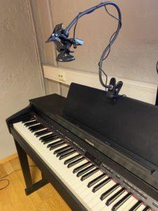 et kamera på stativ over pianotangentene