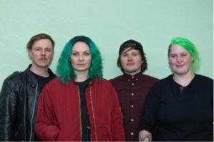 et bilde av bandet Sassy Kraimspri, alle fire ser inn i kameraet og smiler