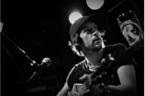 et sort hvit bilde av Ola Håkon mens han spiller gitar