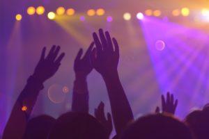 bilde fra publikum av en konsert, hvor man ser bare hender og lys